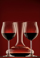 Two glasses of red wine and decantor on red background