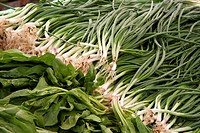 Fresh green onions on a counter in an open marketplace