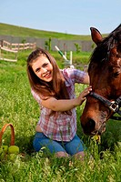 attractive girl feeding horse. outdoor shot