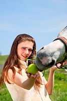 attractive girl feeding a horse apples. outdoor shot