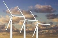 Three Wind Turbines Over Dramatic Blue Sky