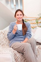 Portrait of a woman holding a cup of coffee in her living room
