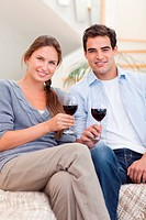 Portrait of a young couple having a glass of red wine in their living room