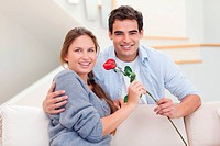 Young man offering a rose to his wife in their living room
