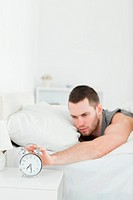 Portrait of a young man being awakened by an alarm clock in his bedroom