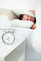 Portrait of a young man covering his ears with a pillow while his alarm clock in ringing