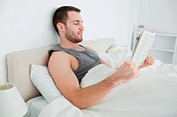 Beautiful man reading a newspaper in his bedroom