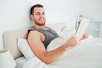 Smiling young man reading a newspaper in his bedroom