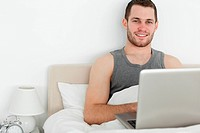 Handsome man using a laptop in his bedroom