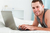Happy man using a laptop while lying on his belly in his bedroom