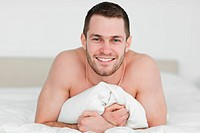 Smiling man lying on his bed while looking at the camera