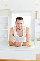 Portrait of a happy man having breakfast in his kitchen