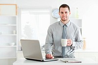 Businessman using a notebook while drinking coffee in his kitchen