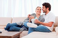 Young couple having a cup of coffee in their living room
