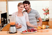 Couple making fresh fruits juice in their kitchen