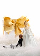 Wedding cake figures with gold ribbon gift on whit