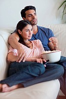 Portrait of a couple watching television while eating popcorn in their living room