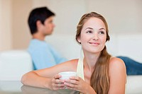 Woman drinking coffee while her fiance is sitting on a couch in their living room