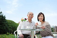 Mature couple having tea outdoors