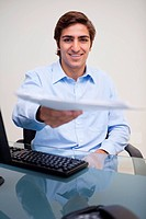 Smiling young businessman handing over paperwork