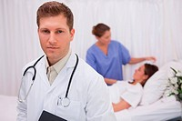 Doctor standing in his patients room with patient and colleague behind him