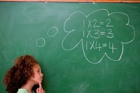 Schoolgirl thinking about algebra in front of a blackboard