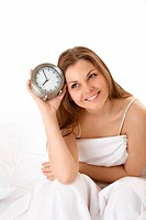 The smiling young woman with an alarm clock