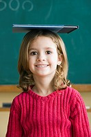 Portrait of girl 6_7 balancing book on head