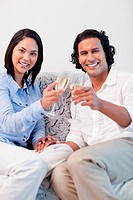 Happy young couple drinking sparkling wine on the sofa