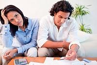 Sad young couple checking their bills