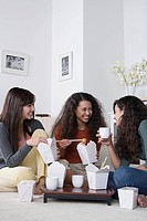 Young women eating take out food at home