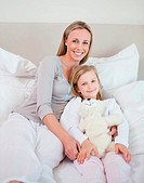 Mother and daughter sitting together on bed