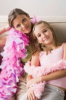 Portrait of mother and daughter 10_11 wearing feather boa at slumber party