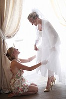 Woman helping bride get dressed