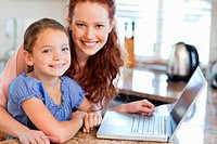 Mother and daughter together with notebook in the kitchen