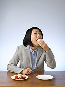 Businesswoman eating donut at desk