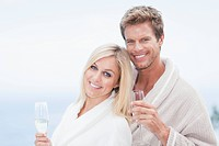 Couple in bathrobes hugging outdoors
