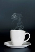 white cup with hot liquid and steam