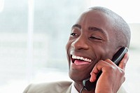 Close up of a laughing businessman on the phone in his office