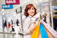 Attractive smiling curly woman on shopping with a credit card