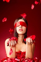 Charming girls blindfold with falling petals of roses on a red background