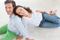 Portrait of smiling couple sitting on floor (thumbnail)