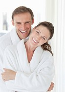 Portrait of smiling couple hugging in bathrobes