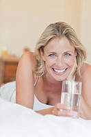 Portrait of smiling woman laying on bed with glass of water