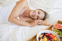 Portrait of smiling woman laying on bed near tray of fruit