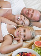 Portrait of smiling parents and daughter laying on bed near tray of fruit