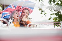 Happy couple with British flag umbrella riding double decker bus