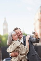 Couple taking self_portrait with digital camera in city