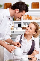 The young waiter with the client in cafe