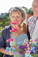 Senior couple smelling flowers in garden